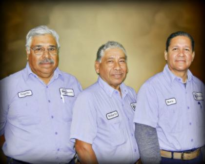 Three men in work uniform shirts posing for a picture
